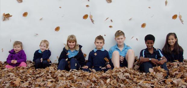 children sitting amongst autumn leaves